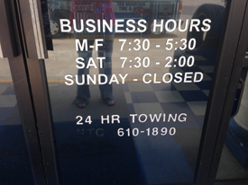 Business hours in white on glass door
